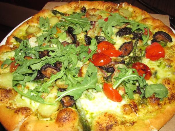 Spring Pizza with grilled asparagus, wild mushrooms, baby red potatoes, pesto, oven-dried tomatoes, and fresh arugula.