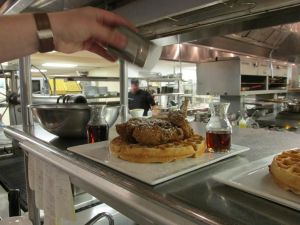 Chef Kelley Schmidt puts the finishing touches on an order of chicken & waffles.
