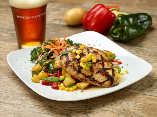 GRILLED BEER-GLAZED CHICKEN (570 CAL) Grilled chicken breast over roasted potatoes and sautéed peppers & onions, topped with corn and green onions. served with apple & kale coleslaw.